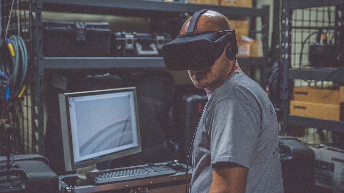 Technician wearing a VR mask while working on a computer.